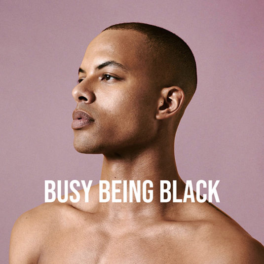'Busy Being Black' host, Josh Rivers, looks to the left. Pink background.